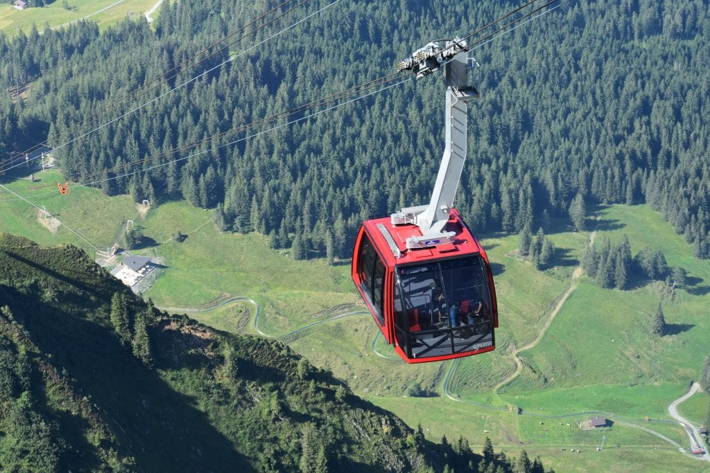 red gondola to Pilatus Kulm over green mountain