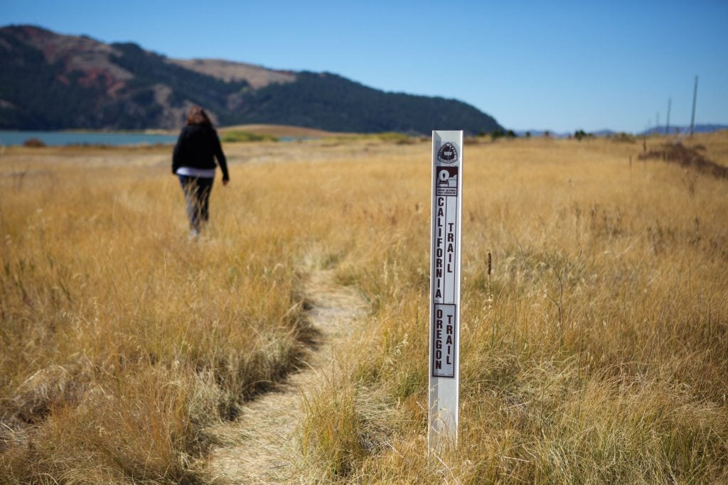 trail signs in brown grass with blue lake and brown mountains