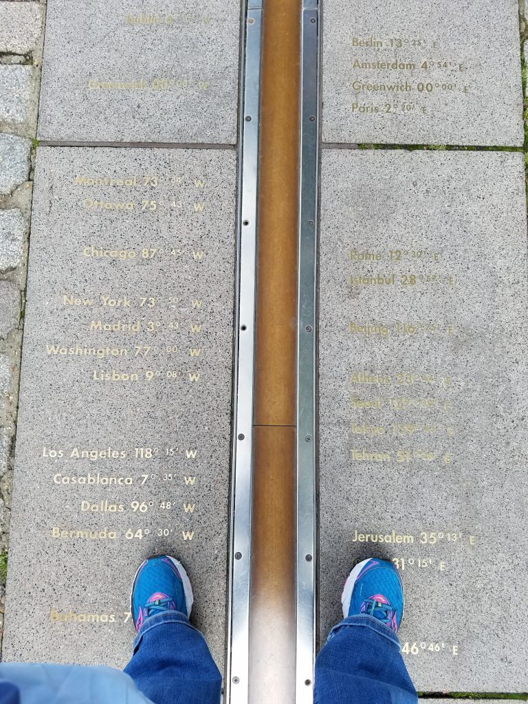 gold prime meridian with blue shoes on either side of line