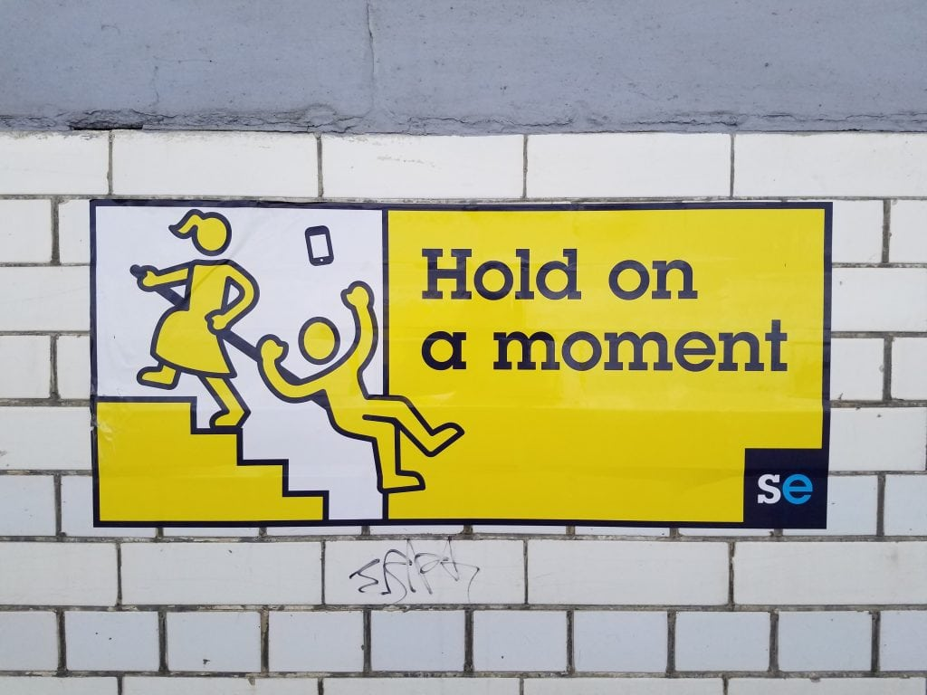 yellow sign on white tile wall in London tube station