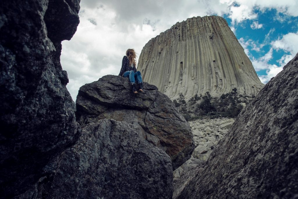 Woman looking up at blue skies and Devil's Tower National Monument