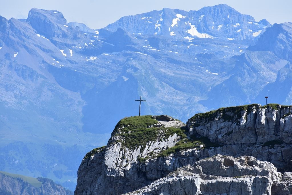swiss alps with cross on mountain top