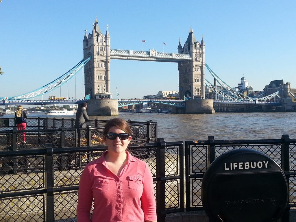 woman in pink shirt and sunglasses in front of river front with tower bridge in background