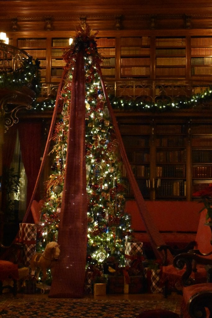 christmas tree in large library with red sofa and chairs