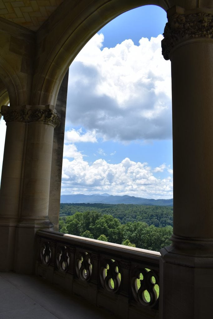 mountains, blue sky, and green forest framed by stone columns and railing