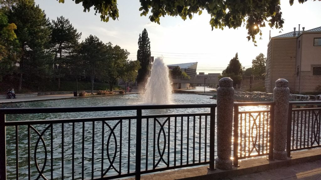 green tree lined Indianapolis canal walk with black iron fence and water fountain at sunset