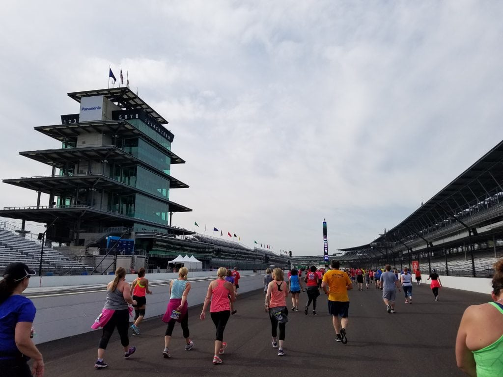 multiple people running along black race track with Indianapolis Motor Speedway tower on left