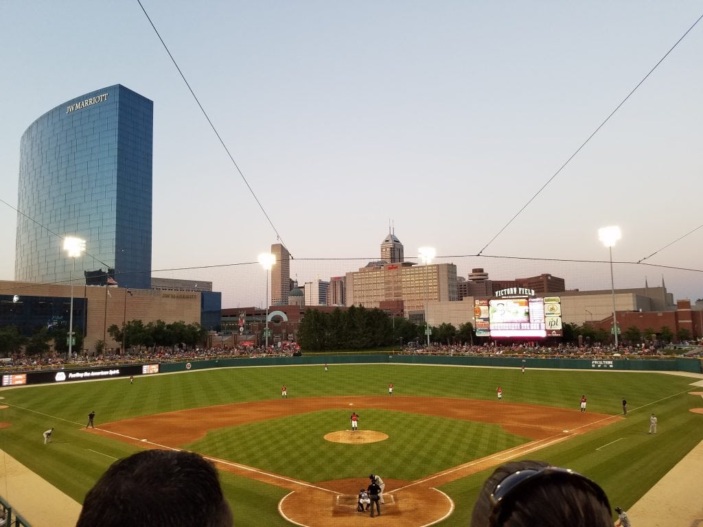 green baseball diamond under lights with city skyline in background at dusk