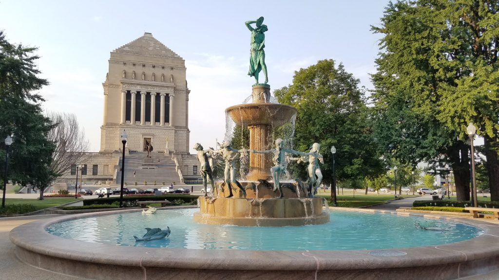 white stone Indianapolis War Memorial and nearby fountain with aqua blue water and water nymph statues