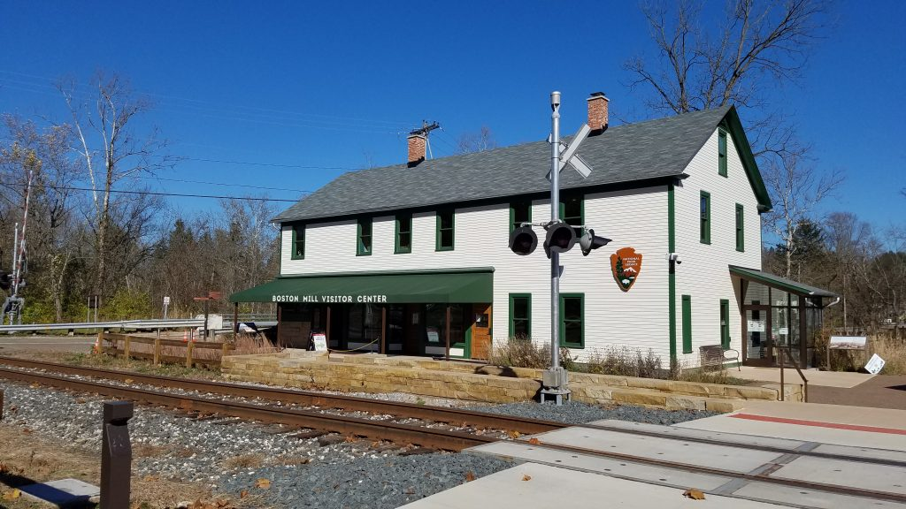 white cuyahoga valley national park visitor center building trimmed in green with railroad tracks and crossing in the foreground