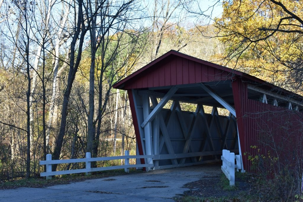 red and white wooden covered bridge in a forest during fall