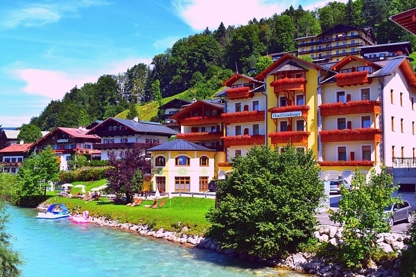 Colorful buildings of the town of Berchtesgaden, Germany on a green mountainside and next to a clear blue river