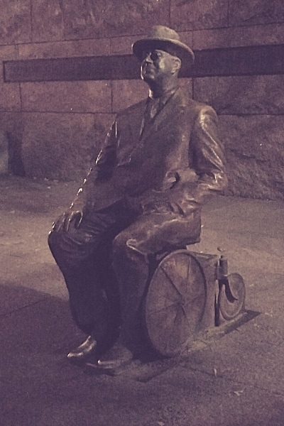 Metal statue of Franklin Delano Roosevelt seated in wheelchair as seen at night