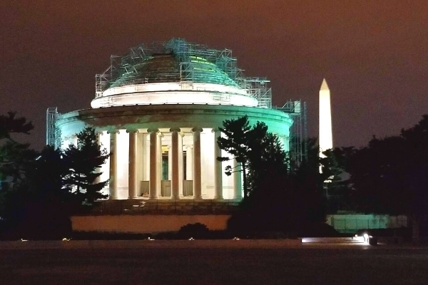 Jefferson and Washington Monuments at night, with scaffolding covering the Jefferson Memorial dome