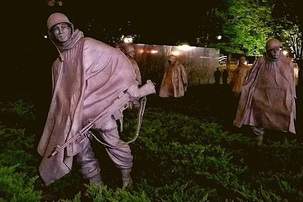 Metal statues of life-sized soldiers at the Korean War Veterans Memorial at night