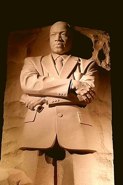 Stone statue of Martin Luther King, Jr.  lit at night at his memorial on the National Mall in Washington, DC, a perfect national park site to visit for Black History Month