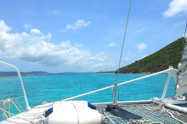 White ship rigging with aqua blue ocean, blue skies, and Buck Island in St Croix