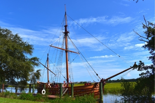 Replica 17th century light trading ship christened the Adventure, moored at a dock on the river