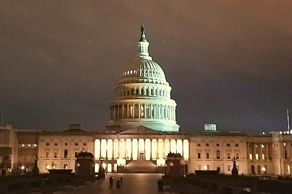 US Capitol building lit up against a cloudy night sky