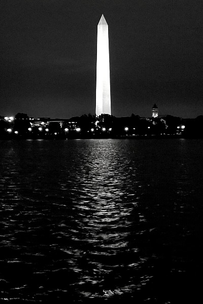 Black and white photograph of the Washington Monument at night reflected in the Tidal Basin waters