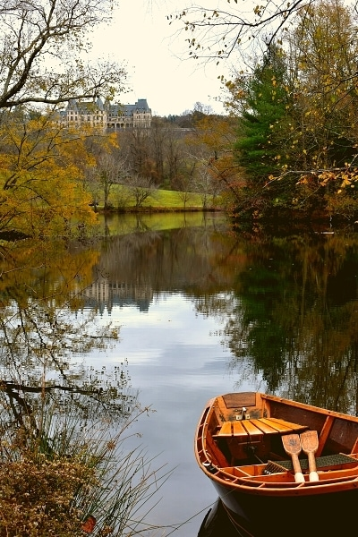 Rowboat on the Lagoon at the Biltmore Estate with fall trees and the Biltmore House reflected in the water