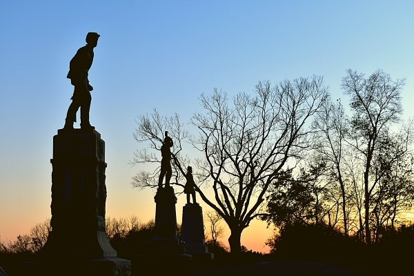 Battlefield Memorials at Antietam National Battlefield are black against the sun setting behind the trees