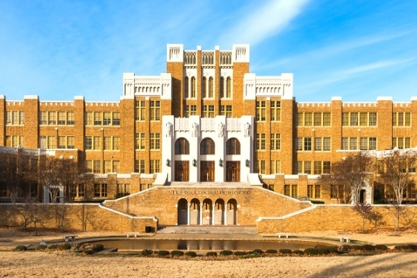 Front entrance of Little Rock Central High School, brick and stone building with reflection pool in foreground and blue sky above.