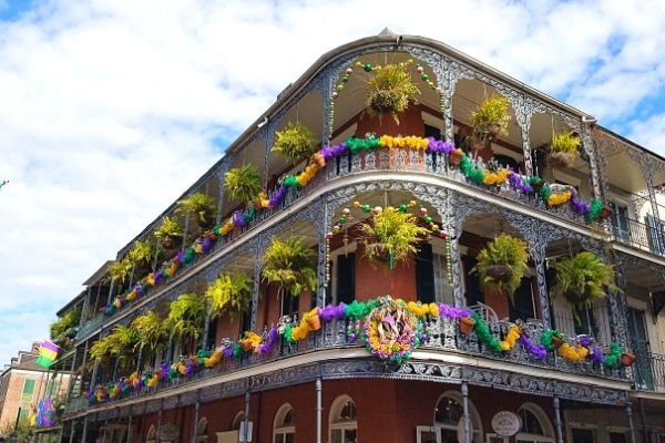 Yellow, green, and purple tulle and buntings decorate a New Orleans French Quarter multi-story building in February