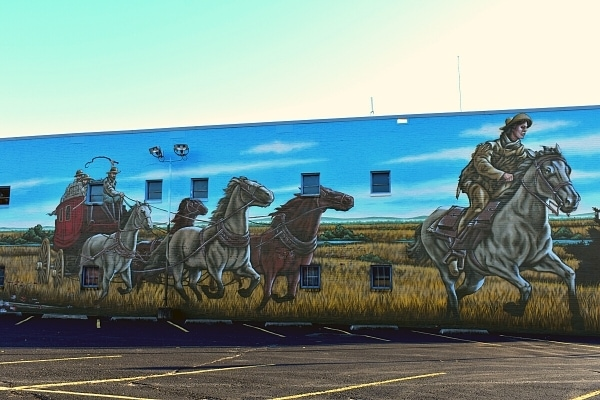 Pony Express mural of horse carriages and a messenger rider on the side of a building in St Joseph, Missouri