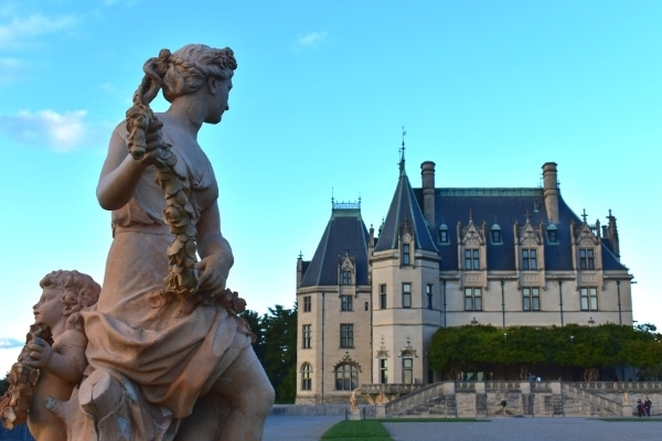 Stone statue of a garden nymph and cherub overlook the South Terrace to the Biltmore House and the vined-covered Library Terrace.