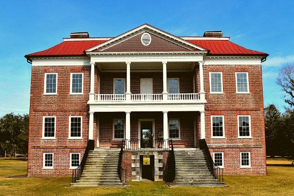 Three story brick plantation home with double covered porches and twin staircases dominates the Drayton Hall plantation