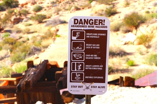 Abandoned mine danger sign in front of old mine ruins in the desert of Joshua Tree National Park