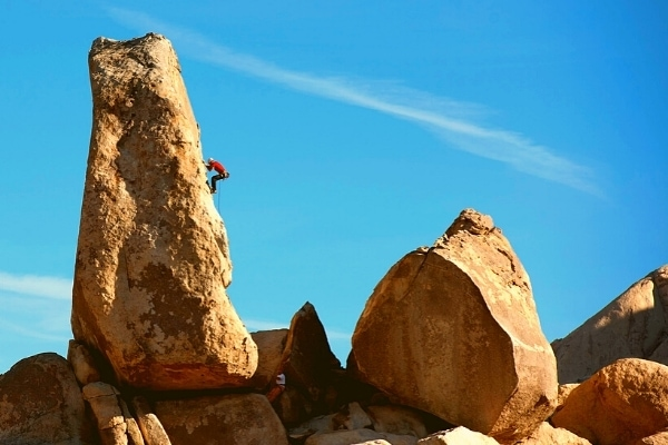 Large boulders perfect for rock climbing at Joshua Tree National Park with a single climber in red shirt halfway up a vertical rockface
