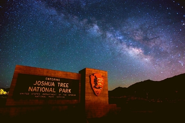 Starry deep blue milky way sky with a Joshua Tree National Park sign in the foreground
