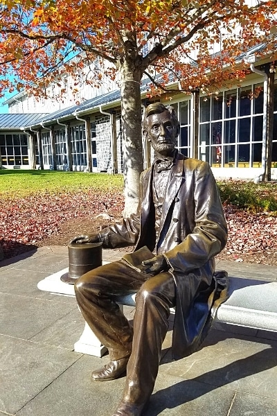 Seated bronze statue of Abraham Lincoln with his hat at his side and the Gettysburg Address in his hands, on a bench at the Gettysburg National Military Park Visitor Center