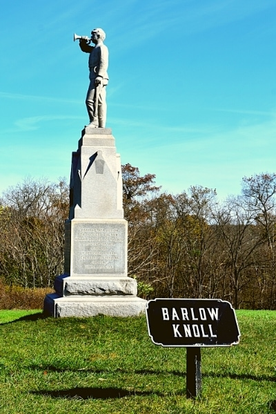 A stone memorial to Civil War soldiers, topped by a bugler soldier, sits atop Barlow Knoll at Gettysburg Battlefield