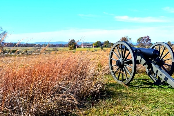 A cannon peers through tall yellow grass across Gettysburg Battlefield under a blue sky