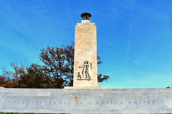 """The inscription in the stone base of the Eternal Peace and Light Memorial at Gettysburg Battlefield proclaims, """"Peace Eternal in a Nation United"""" as another stone column rises from the center and is topped with an eternal flame"""