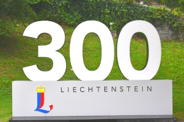 """Large person-sized sign reading """"300 Liechtenstein"""" with the Liechtenstein logo is set up to celebrate the country's anniversary"""