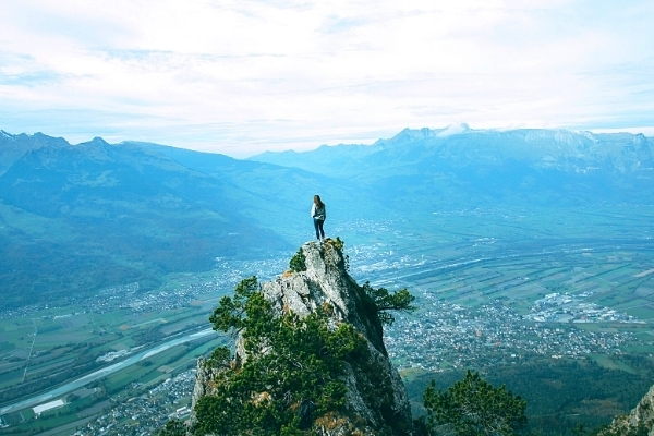 A lone hiker stands atop a rocky outcropping in the mountains above the Rhine River and Liechtenstein