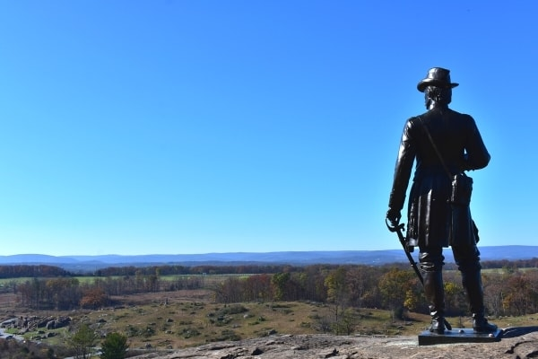 Metal statue of Union engineer and Brigadier General Warren stands atop Little Round Top hillside, gazing down at Devil's Den and the Gettysburg Battlefield