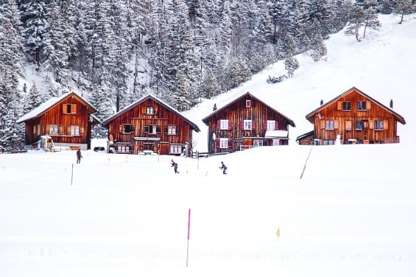 Skiers cruise through the thick snow in front of 4 wooden ski chalets in the snow covered woods of Malbun, Liechtenstein