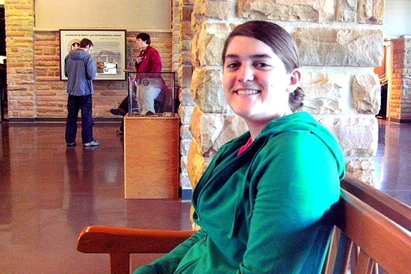 A woman in a green jacket smiles from a brown bench in the lobby of the Mammoth Cave National Park Visitor Center