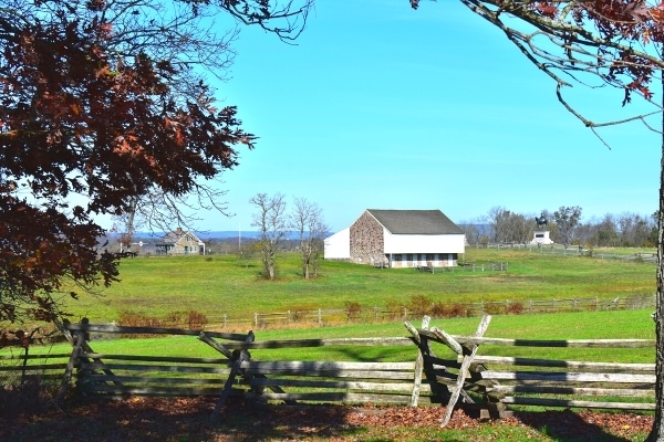 White and brown McPherson Barn surrounded by green fields, wooden fences, and a blue sky at Gettysburg Battlefield