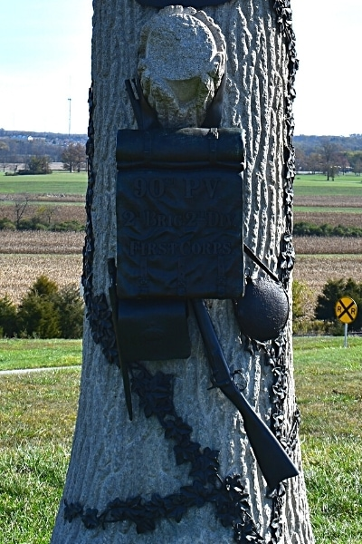 Intricately carved stone and metal memorial made to look like a solider's pack hanging on a tree remembers Union soldiers at Oak Ridge at Gettysburg