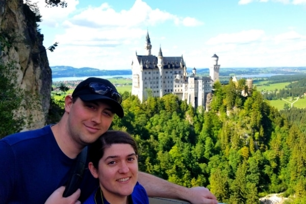A couple smile for the camera with Neuschwanstein Castle, a green forest, and blue skies in the background