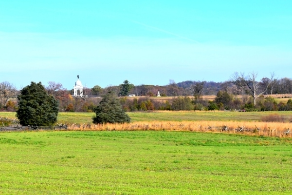 Green field and tall yellow grass surround Plum Run At Gettysburg Battlefield with the white stone Pennsylvania Memorial in the distance