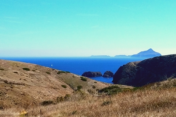 Yellow grassy hills of Santa Cruz island look out across the blue Santa Barbara Channel at Anacapa Island in the distance