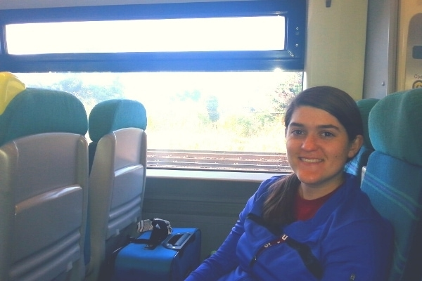 A woman in a blue jacket smiles from her seat on the train