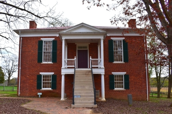 The Appomattox County Court House is a square two-story red brick building with a covered second-floor entrance